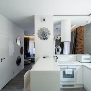 Kuchnia otwiera się na salon z jadalnią. Wcześniej stała tu ściana. Właściciel zdecydował się ją usunąć, tak by optycznie powiększyć wnętrze. Ścianę zastąpiono białymi meblami, które wyraźnie wyznaczają strefy mieszkalne. Zdjęcia: Nowa Papiernia, Fot. Maciej Lulko