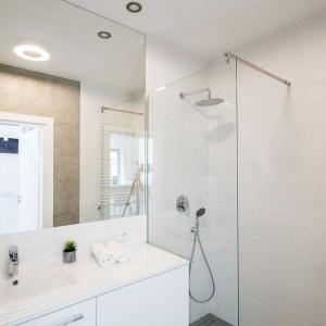 Projekt łazienki łączy różne materiały, które stanowią bardzo zgrabny zestaw. Na ścianach białe płytki zestawiono z betonem. Nie mają wzorów i drastycznych różnic fakturowych, dlatego nie rywalizują ze sobą, za to stanowią dla siebie naturalne tło. Zdjęcia: Nowa Papiernia, Fot. Maciej Lulko