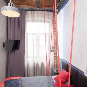 Czerwone liny rozpostarte między sufitem, a łóżkiem, dają wrażenie, jakby mebel unosił się nad podłogą. Fot. Bartosz Jarosz