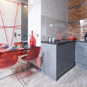 W salonie znalazło się również miejsce na jadalnię. Lekki konstrukcyjnie stół doskonale wpisuje się w klimat wnętrza. Nie mogło przy nim zabraknąć również motywu czerwonego – nowoczesnych krzeseł z plexi. Fot. Bartosz Jarosz
