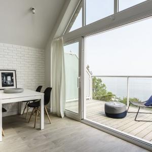 Morską panoramę najlepiej ogląda się z drewnianego tarasu, który dzięki podobnej posadzce w obu strefach jest naturalnym przedłużeniem salonu.  Fot. FOTO&MOHITO