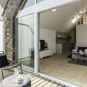 Panoramiczne okno oraz jednorodność kolorystyczna tarasu i wnętrza mieszkania zaowocowały jego znacznym optycznym powiększeniem. Fot. FOTO&MOHITO