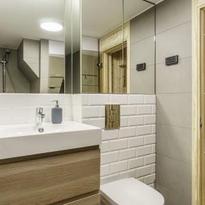 W aranżacji dominuje jasne drewno.  W łazience szare płytki połączono z tradycyjnymi białymi kaflami.  Fot. FOTO&MOHITO