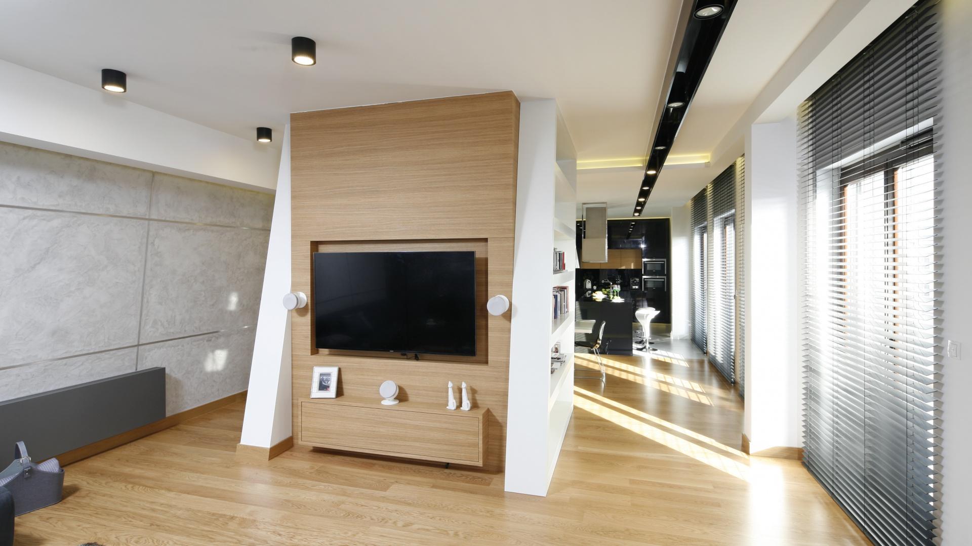 Otwartą część dzienną dzieli element konstrukcyjny budynku. Od strony wypoczynkowej zamontowano na nim telewizor, który można oglądać siedząc na wygodnej kanapie. Element konstrukcyjny wykończony jest fornirem dębowym. Projekt: Monika i Adam Bronikowscy. Fot. Bartosz Jarosz
