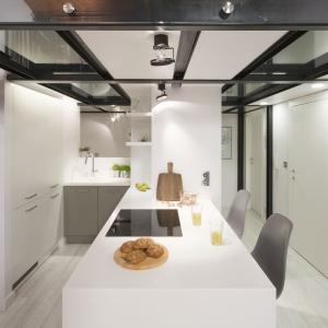 Kolorystyka kuchni jest spójna z wystrojem całego apartamentu, dzięki czemu pozostaje ona subtelnym tłem dla salonowej aranżacji. Projekt: Szymon Chudy. Fot. Bartosz Jarosz