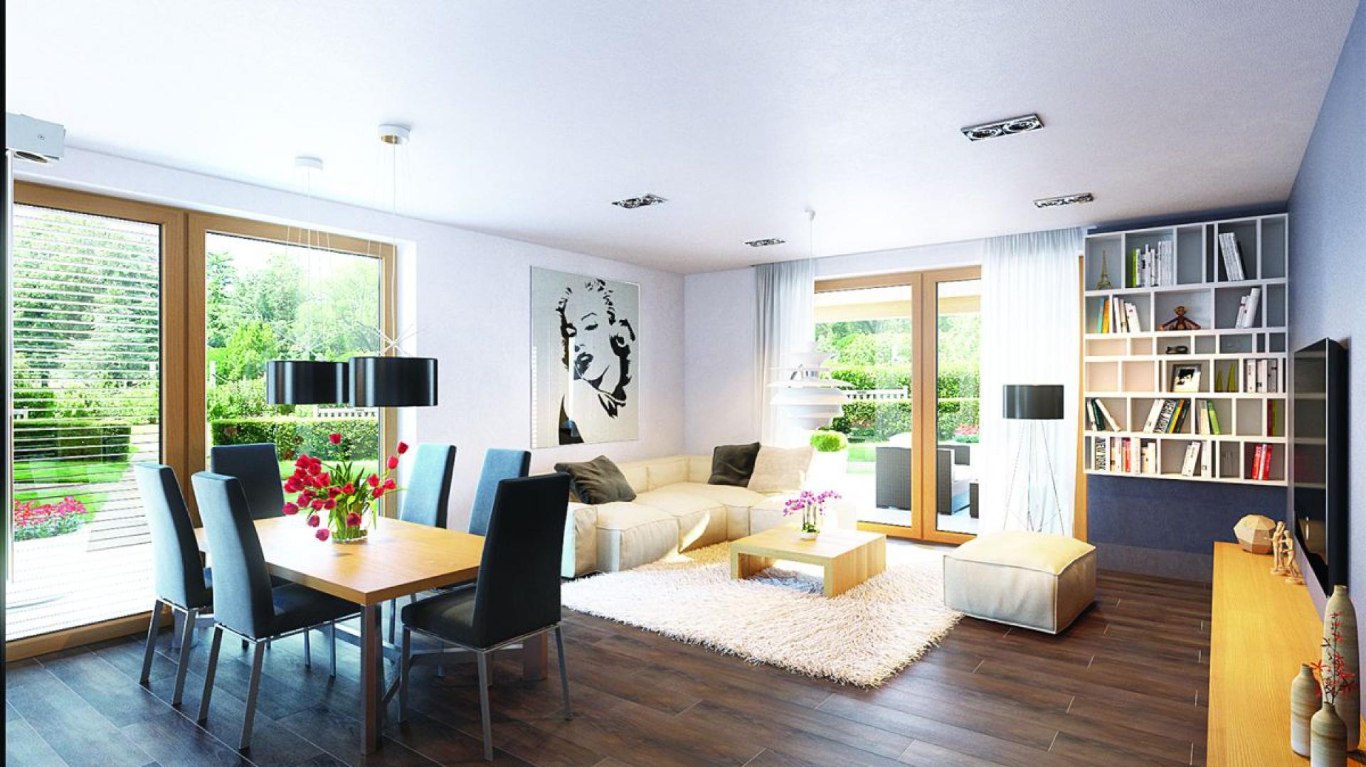 Salon połączony z jadalnią jest jasny i przestronny - głównie dzięki dużym przeszkleniom i bieli ścian. Całość ociepla drewniana podłoga o czekoladowym zabarwieniu. Projekt: Kornel VI (z wiatą) ENERGO, Fot. Pracownia Projektowa Archipelag