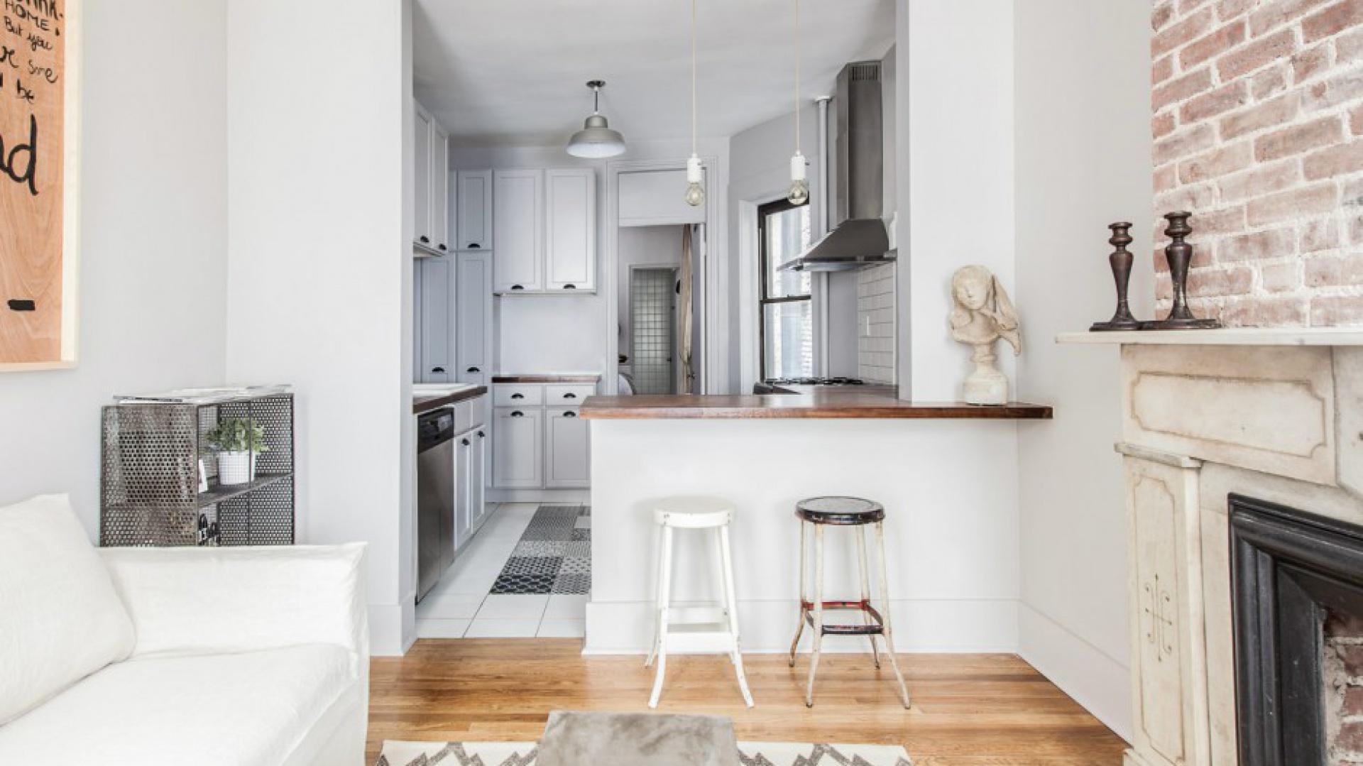 Kuchnię wpasowano we wnękę, połączoną z sypialnią, za którą w rzędzie umieszczono łazienkę. Salon od kuchni oddziela barek śniadaniowy, przy którym ustawiono lekkie, metalowe stołki. Projekt: Fanny Abes, The New Design Project. Fot. Alan Gastelum.