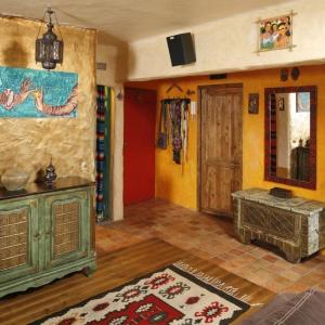 W tym przedpokoju o sporym metrażu ściany to wielokulturowa mozaika. Pamiątki z Egiptu, Tunezji, Tajlandii, Indii, Meksyku, Kuby pięknie prezentują się na tle złotych i pomarańczowych ścian. Projekt: Dorota i Michał Ługowoj. Fot. Bartosz Jarosz