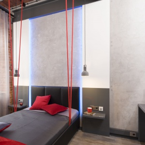 Sypialnie w lofotowym klimacie. Czerwone liny rozpostarte między łóżkiem a sufitem dają wrażenie jakby mebel unosił się nad podłogą. Projekt: Małgorzata Chabzda. Fot. Bartosz Jarosz