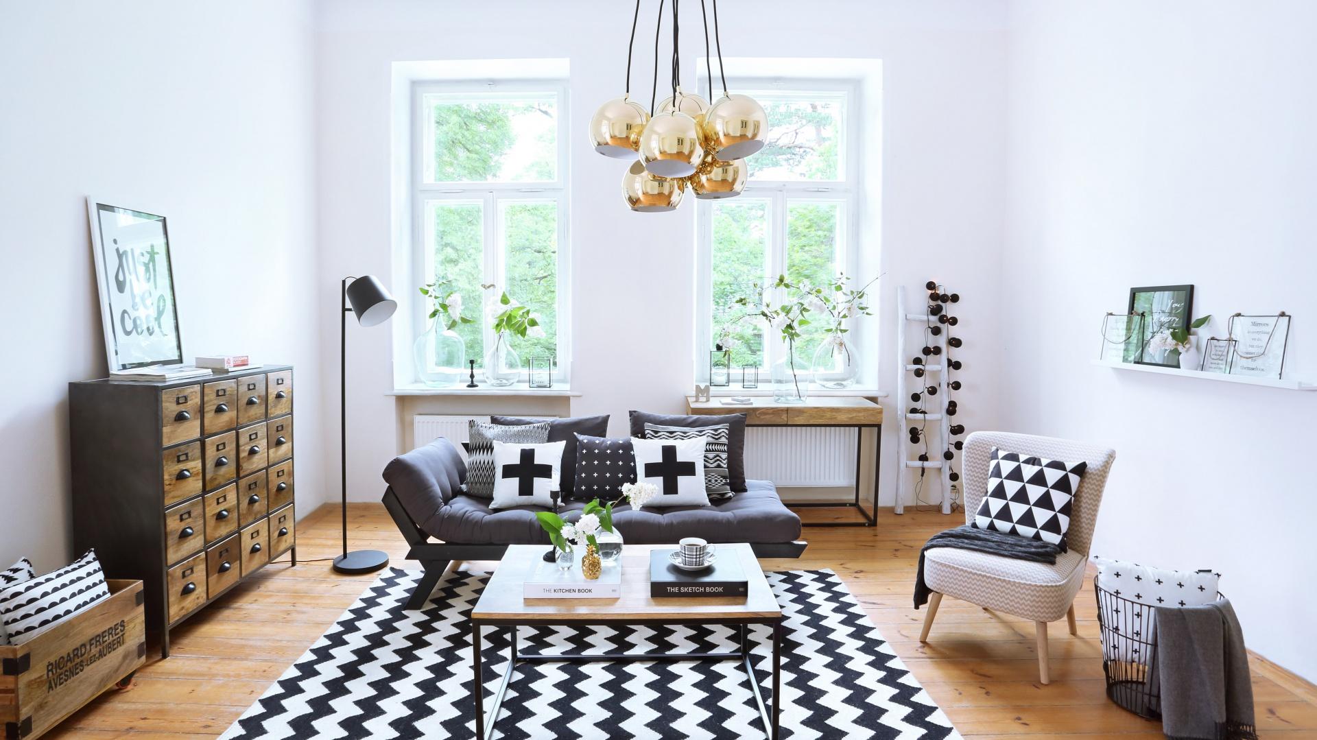Poszewka na poduszkę HOLIC oraz dywan ZIG ZAG III z graficznym wzorem uzupełnią modną aranżację salonu utrzymaną w czarno-białej stylistyce. 169 zł i 719 zł. Fot. Westwing