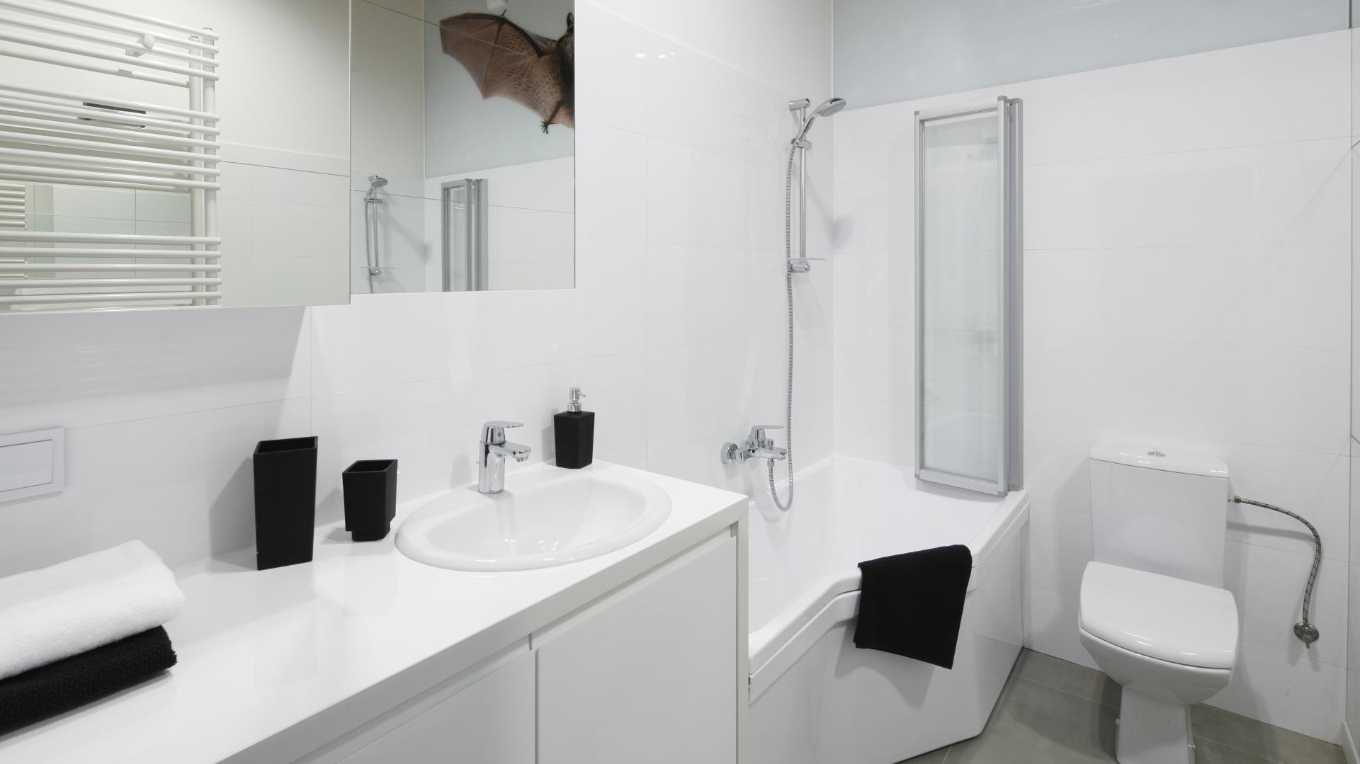 Rozwiązanie dwa w jednym, czyli prysznic połączony z wanną to zawsze dobre rozwiązanie w małej łazience. Jasne kolorystyka dodatkowo powiększa przestrzeń. Projekt: Tomasz Jasiński. Fot. Bartosz Jarosz