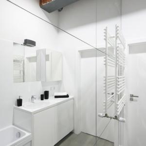 Przestrzeń niedużej łazienki optycznie powiększają ogromne tafle luster. Projekt: Tomasz Jasiński. Fot. Bartosz Jarosz