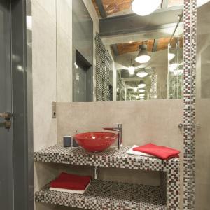 Styl łazienki jest kombinacją matowej szarości betonowych ścian i połyskującej mozaiki z motywem czerwieni. Projekt: Małgorzata Chabzda. Fot. Bartosz Jarosz
