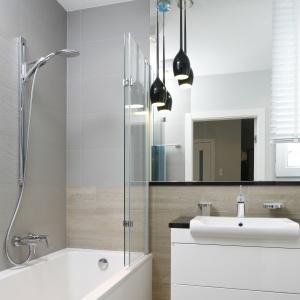 Łazienka jest niewielka, więc prysznic połączony został z wanną. Szklana ścianka oddzielająca strefę kąpieli od Projekt: Joanna Morkowska-Saj. Fot. Bartosz Jarosz
