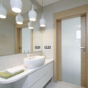 Duże lustro, podobnie jak jasna kolorsytyka optycznie powiększa wnętrze łazienki. Projekt: Renata Modrzyńska-Kasiak. Fot. Bartosz Jarosz