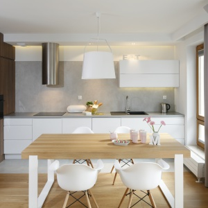 Zabudowa kuchenna to połączenie dwóch materiałów: białego, lakierowanego MDF-u oraz dębowego forniru. Gładkie powierzchnie frontów i blatów wprowadzają do wnętrza pokój i harmonię. Projekt: Przemek Kuśmierek. Fot. Bartosz Jarosz
