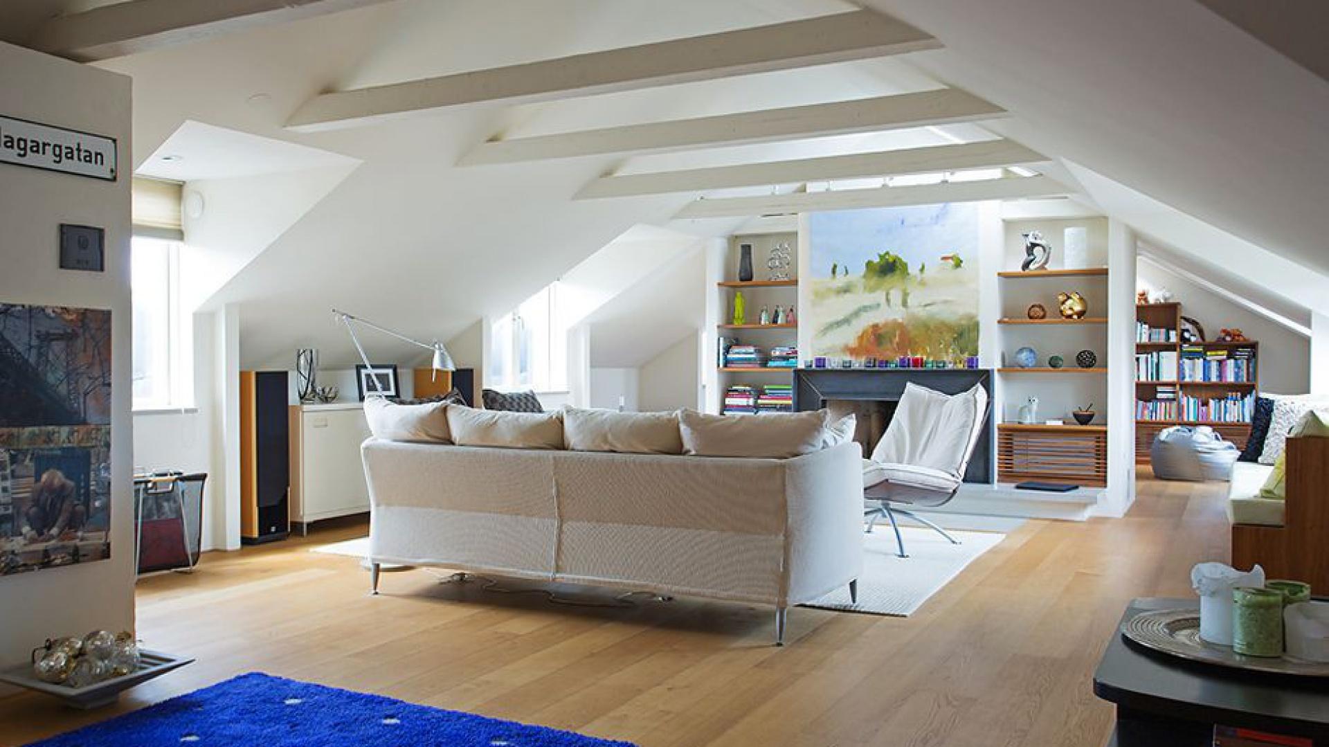 Przestrzeń w mieszkaniu zaaranżowano z pomysłem. Za ścianką działową, na której zlokalizowano kominek urządzono pokój telewizyjny z biblioteczką. Fot. Per Jansson.