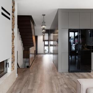 Ekstrawagancji i nowoczesności dodaje spokojnym barwom czerń, która jest tu wyrazistym leitmotivem. Pojawia się w kuchni (elementy zabudowy, sprzęt AGD, okap), salonie (lampy, TV, obudowa kominka), a najbardziej intensywnie w niewielkiej łazience. Fot. Archissima/Dekorian