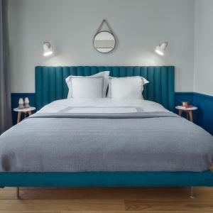 W sypialni uwagę zwraca duże, komfortowe łóżko firmy NAP w intensywnym, turkusowym kolorze. Jego kontynuacją jest ciemnoniebieska, niska lamperia. Fot. JTgrupa