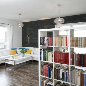 Salon ożywiają barwne dodatki. Ciekawym pomysłem na podzielenie niewielkiego wnętrza jest biblioteczka. Projekt: Katarzyna Uszok. Fot. Bartosz Jarosz