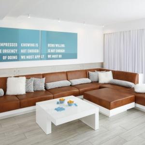 Niezwykle jasny salon, którego wyjątkową ozdobą są wyraziste brązowe meble i chłodno-niebieski obraz z modnymi napisami. Projekt: Dominik Respondek. Fot. Bartosz Jarosz