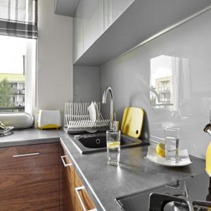 Ścianę nad blatem w kuchni wykończono szkłem w szarym kolorze, dzięki czemu po codziennym gotowaniu można było szybko i łatwo zaprowadzić porządek w kuchni. Fot. Bernard Białorucki