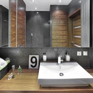 Fornirowana zabudowa kryje wiele schowków i półek, dzięki którym mała łazienka jest praktyczna. Duża tafla lustra optycznie ją powiększa. Fot. Bernard Białorucki
