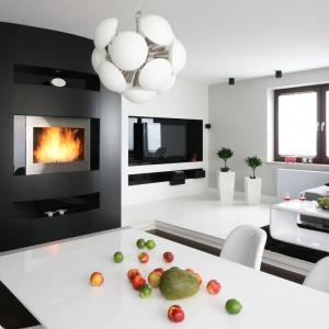Na tle białego wnętrza okazale prezentuje się czarna ściana z kominkiem. Projekt: Agnieszka Burzykowska-Walkosz. Fot. Bartosz Jarosz