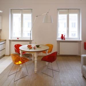 Białe wnętrze ożywa dzięki złocistopomarańczowym krzesłom. Projekt: Agnieszka Żyła. Fot. Bartosz Jarosz