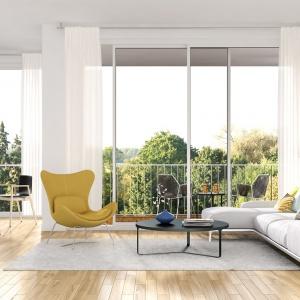 Biały kolor ścian w połączeniu z ogromnymi przeszkleniami sprawiają, że wnętrze wydaje się niezwykle przestronne i pełne światła. Fot. Dekoral