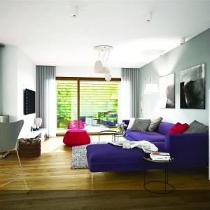 Minimalistyczne wnętrze salonu ociepla drewniana podłoga. Dodatkowo ożywia ją soczyście fioletowa kanapa.  Projekt: Riko III G2, autor: arch. Artur Wójciak, Fot. Pracownia Projektowa Archipelag