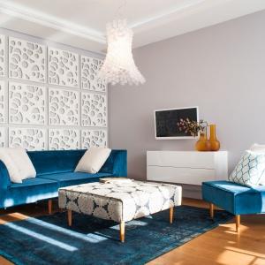 Pokój dzienny skomponowano z bieli i różnych odcieni niebieskiego. Turkusowe meble wypoczynkowe pięknie kontrastują z oryginalnymi, ażurowymi panelami na ścianie. Projekt: Arkadiusz Grzędzicki. Fot. Adam Ościłowski