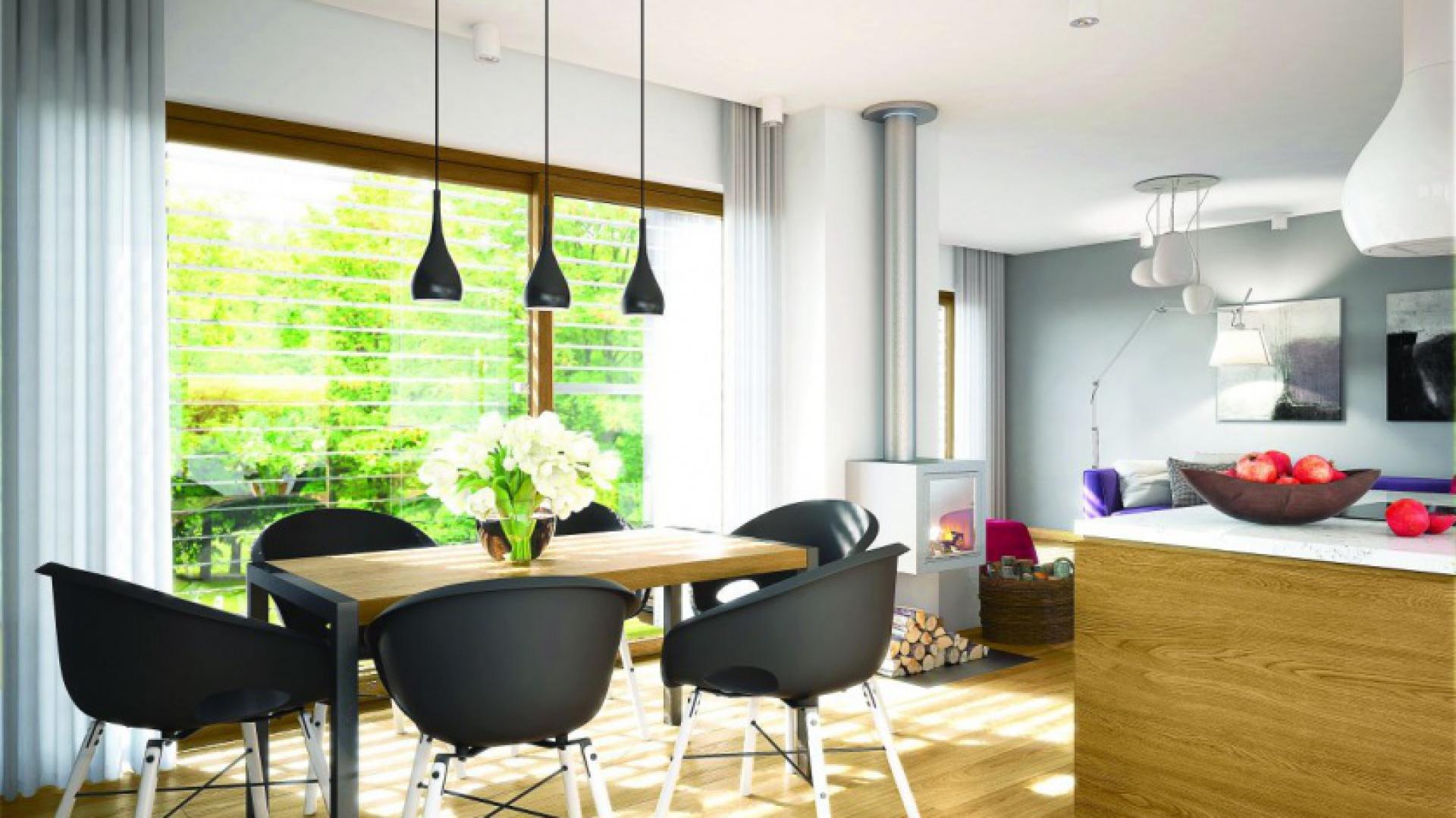 Sercem domu jest przestrzeń dzienna, złożona z salonu, jadalni i kuchni. Jasne ściany i duże przeszklenia dają wnętrzu mnóstwo światła. Projekt: Riko III G2, autor: arch. Artur Wójciak, Fot. Pracownia Projektowa Archipelag