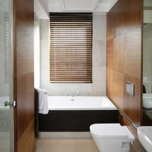 Wąska łazienka z wanną i sporą ilością miejsca na przechowywanie, które ukryto za drewnianymi frontami. Projekt: Małgorzata Mazur. Fot. Bartosz Jarosz