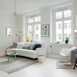 W białym salonie uwagę przyciąga ściana wykończona w całości cegłą. Wprowadza do wnętrza nieco surowego klimatu, korespondując z industrialnym oświetleniem. Fot. Alvhem Makleri