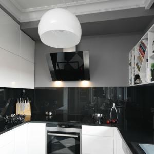 Ścianę nad blatem wykończono szkłem w czarnym kolorze, które doskonale koresponduje z pozostałymi elementami wnętrza. Projekt: Tomasz Motylewski, Marek Bernatowicz. Fot. Bartosz Jarosz