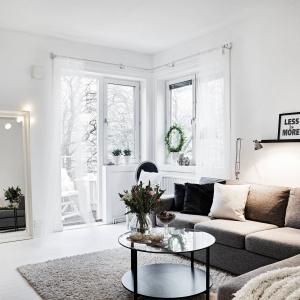 W salonie, sterylną biel przełamują czarne dodatki oraz duży, szary narożnik. Fot. Stadshem.se/Janne Olander