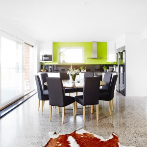 Jadalnia z kuchnią stanowią jedną, wspólną przestrzeń. Czarne szkło nad blatem kuchennym komponuje się z czarnym blatem stołu oraz siedzeniami i oparciami krzeseł. Fot. Vastanhem