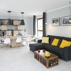 Czarna narożna kanapa pięknie wkomponowała się w jasnoszare wnętrze. Dodatkowym akcentem kolorystyczny są tu modne, żółte poduchy. Projekt: Maciejka Peszyńska-Drews. Fot. Bartosz Jarosz