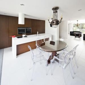 Aranżacja wnętrz łączy nowoczesność z elementami klasycznymi. W kuchni wyróżnia się wysoka zabudowana w ciemnym drewnie i nowoczesna wyspa. Fot. Fotoarchitektura Anna Gregorczyk