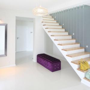 Głównym elementem dekoracyjnym przedpokoju są piękne schody jednobiegowe. Akcentem kolorystycznym jest fioletowy puf. Projekt: Karolina i Artur Urba. Fot. Bartosz Jarosz