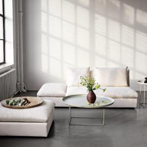 Minimalistyczne wnętrza lubią proste bryły mebli. Stolik na cienkich nogach, którego blat ma kształt tacy, sprawdzi się doskonale. Fot. Houseology