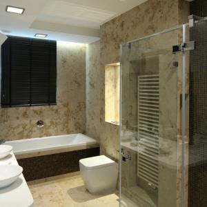 Płytkami kamiennymi wykończono niemal całą łazienkę. Beżowy kamień z charakterystycznym, dekoracyjnym wzorem pięknie koresponduje z brązową mozaika. Projekt: Katarzyna Koszałka. Fot. Bartosz Jarosz