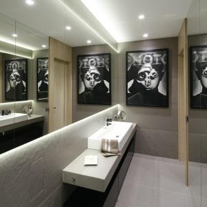 Ściany w łazience pokrywają ogromne lustra oraz płytki w szarym kolorze. Projekt: Małgorzata Muc, Joanna Scott. Fot. Bartosz Jarosz