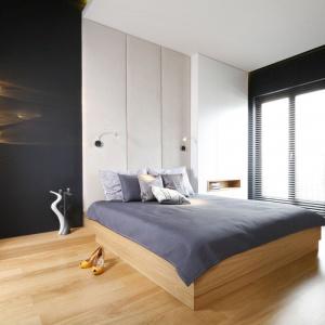 W tej sypialni wyróżniają się lampy zawieszone w boku. Cieple żółte światło pięknie kontrastuje z czarnym kolorem ścian. Uzupełnieniem oświetlenia są delikatne lampki nocne.  Projekt: Monika i Adam Bronikowscy. Fot. Bartosz Jarosz