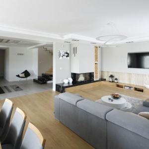Biało-szary salon zdecydowanie ociepla drewniana podłoga i meble w słomkowym odcieniu drewna. Projekt: Katarzyna Mikulska-Sękalska. Fot. Bartosz Jarosz