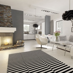 W tym biało-czarnym wnętrzu zaproponowano strefę dzienna w postaci open space'u. Kuchnia została delikatnie odseparowana za pomocą niewielkich ścianek. Fot. Archeco Dom dla Ciebie