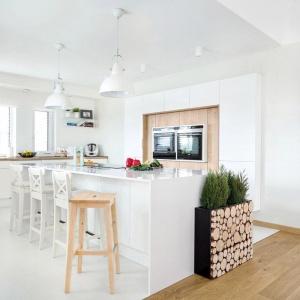 W białej kuchni zabudowa wokół piekarnika została wykończona jasnym drewnem. Fot.  Studio Vigo, Max Kuchnie