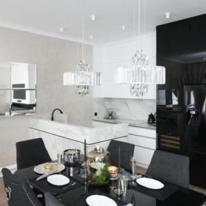 Każda ze stref funkcjonalnych zaznaczona jest odrębnym kolorem mebli: jasne w salonie, czarne w jadalni po piękny, marmur w kuchni. Projekt: Karolina Łuczyńska. Fot. Bartosz Jarosz