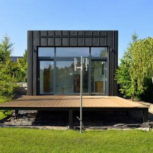 W domu jednoosobowym znalazło się też miejsce na przestronny taras. Wykończono go drewnem, co ociepla wizerunek szklano-metalowej bryły domu. Projekt: arch. Tadeusz Lemański. Fot. Tomasz Zakrzewski